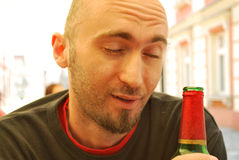Drunk. Young man drinking from a bottle of beer Royalty Free Stock Image
