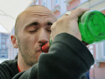 Drunk. Young man drinking from a bottle of beer Royalty Free Stock Photography