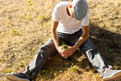 Drunk adult man sitting down on the ground Royalty Free Stock Photos