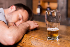 Drunk again. Drunk male customer leaning at the bar counter and sleeping while glass with beer standing near him Royalty Free Stock Photo
