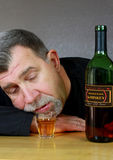 Drunk Alcoholic Adult Man. An alcoholic adult man passed out with a Whiskey bottle and shot glass on a bar Stock Photos