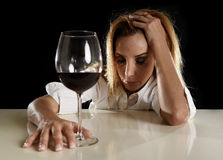 Drunk alcoholic blond woman alone in wasted depressed drinking red wine glass suffering hangover Royalty Free Stock Photo