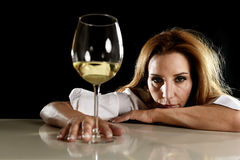 Drunk alcoholic blond woman alone in wasted depressed drinking white wine glass suffering hangover Stock Photo