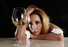 Drunk alcoholic blond woman alone in wasted depressed drinking white wine glass suffering hangover Royalty Free Stock Photo