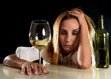 Drunk alcoholic blond woman alone in wasted depressed drinking white wine glass suffering hangover stock photos