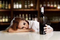 Drunk alcoholic blond woman alone in wasted depressed with red wine bottle in bar Royalty Free Stock Photography