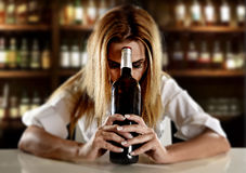 Drunk alcoholic blond woman alone in wasted depressed with red wine bottle in bar Stock Image