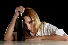 Drunk alcoholic blond woman alone in wasted depressed with red wine bottle suffering hangover Royalty Free Stock Photography
