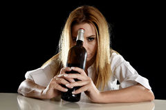 Drunk alcoholic blond woman alone in wasted depressed with red wine bottle suffering hangover Royalty Free Stock Images