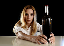 Drunk alcoholic blond woman alone in wasted depressed with red wine bottle suffering hangover Stock Image