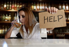 Drunk alcoholic blond woman drinking alcohol asking for help in bar or pub stock photography