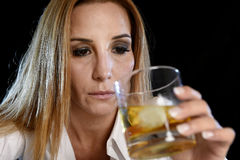 Drunk alcoholic woman alone in wasted depressed face holding and looking thoughtful to scotch whiskey glass Royalty Free Stock Photography