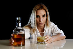 Drunk alcoholic woman alone in wasted  depressed face with scotch whiskey bottle and glass Royalty Free Stock Photo