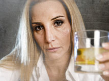 Drunk alcoholic woman wasted and depressed holding scotch whiskey glass drunk Stock Photo