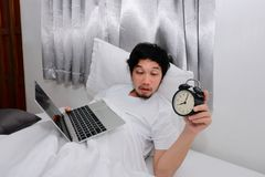 Drunk Asian man with laptop and alarm clock lying down on the bed and having hangover after party. royalty free stock photos