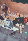 Drunk bearded man lying on floor in messy room Stock Photography