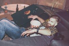 Drunk bearded man lying on floor in messy room Stock Images