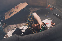 Drunk bearded young man sleeping on couch with bra and beer can Stock Image