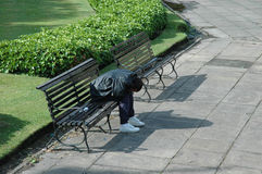Drunk on a bench. A homeless or alcoholic person sleeping on a bench in a public park royalty free stock photography