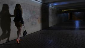 Drunk boozy female walking at night after party. Drunk boozy female in mini skirt and high heeled shoes walking alone in dark underpass tunnel alone. Tipsy woman stock video