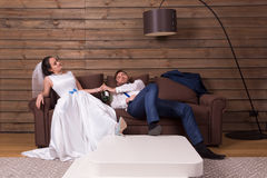 Drunk bride and groom relax on couch after wedding. Drunk bride and groom relax on couch with bottle of alcohol after wedding celebration. Wooden interior of the Stock Image