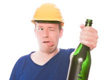 Drunk builder. Intoxicated building worker making a funny face while holding a bottle with alcohol, focus is on the face - isolated on white and retouched Royalty Free Stock Photography