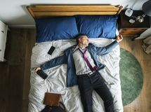 Drunk business man falling asleep as soon as he came back home stock photos