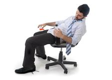 Drunk business man wasted drinking whiskey  in alcoholism problem. Attractive drunk business man sitting leaning back on office chair sleeping wasted holding Stock Images
