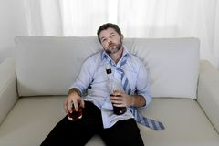 Drunk business man wasted and whiskey bottle in alcoholism. Attractive drunk business man at home lying  on couch at living room wasted  drinking whiskey bottle Stock Photos