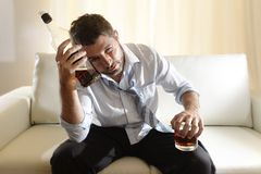 Drunk business man wasted and whiskey bottle in alcoholism. Attractive drunk business man at home sitting on couch at living room wasted  holding whiskey bottle Stock Photos