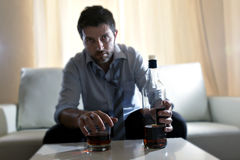 Drunk business man wasted and whiskey bottle in alcoholism. Attractive drunk business man at home sitting on couch at living room wasted  holding whiskey bottle Stock Images