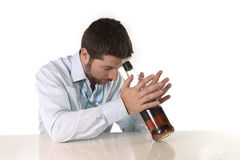 Drunk business man wasted and whiskey bottle in alcoholism. Attractive drunk business man lying on desk wasted and holding whiskey bottle against forehead  in Royalty Free Stock Photography