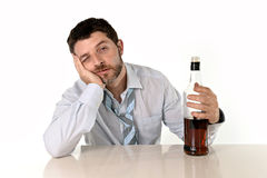 Drunk business man wasted and whiskey bottle in alcoholism. Attractive drunk business man lying on desk wasted and holding whiskey bottle in alcoholism problem Stock Images
