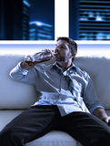 Drunk business man wasted and whiskey bottle in alcoholism concept. Attractive drunk business man sitting on couch wasted  drinking whiskey directly from bottle Royalty Free Stock Photos
