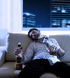 Drunk business man wasted and whiskey bottle in alcoholism concept. Attractive drunk business man sitting on couch wasted drinking whiskey bottle in alcoholism royalty free stock photo