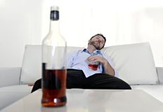 Drunk business man wasted and whiskey bottle in alcoholism. Drunk business man at home lying asleep on couch sleeping wasted holding whiskey glass in alcoholism Royalty Free Stock Photo