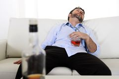 Drunk business man wasted and whiskey bottle in alcoholism. Drunk business man at home lying asleep on couch sleeping wasted holding whiskey glass in alcoholism Royalty Free Stock Images