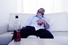 Drunk business man wasted and whiskey bottle in alcoholism. Drunk business man at home lying asleep on couch sleeping wasted holding whiskey glass in alcoholism Stock Photo