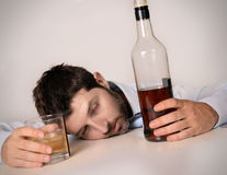 Drunk business man wasted and whiskey bottle in alcoholism. Drunk business man lying on desk wasted and holding whiskey bottle and glass in alcoholism problem royalty free stock photo