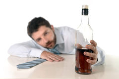 Drunk business man wasted and whiskey bottle in alcoholism. Drunk business man lying on desk wasted and holding whiskey bottle in alcoholism problem , alcohol Stock Photos