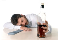 Drunk business man wasted and whiskey bottle in alcoholism. Drunk business man lying on desk sleeping wasted and holding whiskey bottle in alcoholism problem Royalty Free Stock Photo