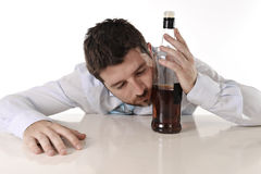 Drunk business man wasted and whiskey bottle in alcoholism. Drunk business man lying on desk sleeping wasted holding whiskey bottle in alcoholism problem Royalty Free Stock Photos