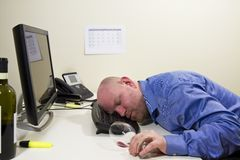 Drunk Businessman. A drunk businessman / office worker sleeping at his computer keyboard royalty free stock photography
