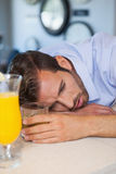 Drunk businessman asleep on bar beside cocktail Stock Image