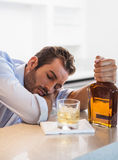 Drunk businessman clutching whiskey bottle asleep Royalty Free Stock Photo