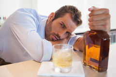Drunk businessman clutching whiskey bottle looking at camera Stock Photos
