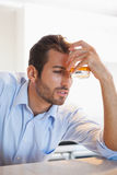 Drunk businessman clutching whiskey glass to forehead Royalty Free Stock Image