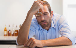 Drunk businessman clutching whiskey glass to head. At the local bar Stock Photos