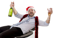 Drunk businessman drinking champagne wearing santa Stock Image