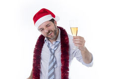 Drunk businessman drinking champagne wearing santa hat at office christmas party Royalty Free Stock Photography